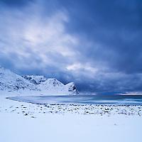 Snow covered beach and winter storm, Unstad, Lofoten islands, Norway