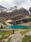 A woman enjoys the view of Oesa Lake with  Glacier Peak and Oesa Glacier (right) in the background, in Yoho National Park, near Field, British Columbia, Canada; MRs available