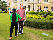 10 JANUARY 2015 - BANGKOK, THAILAND: A Thai government worker carries a life sized cardboard cutout of General Prayuth Chan-ocha, the Prime Minister of Thailand, across the lawn of Government House  during Children's Day festivities at Government House. National Children's Day falls on the second Saturday of the year. Thai government agencies sponsor child friendly events and the military usually opens army bases to children, who come to play on tanks and artillery pieces. This year Thai Prime Minister General Prayuth Chan-ocha, hosted several events at Government House, the Prime Minister's office.     PHOTO BY JACK KURTZ