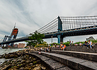 People relax in DUMBO (Down Under the Manhattan Bridge Overpass) with the Manhattan Bridge in background, Brooklyn, New York USA.