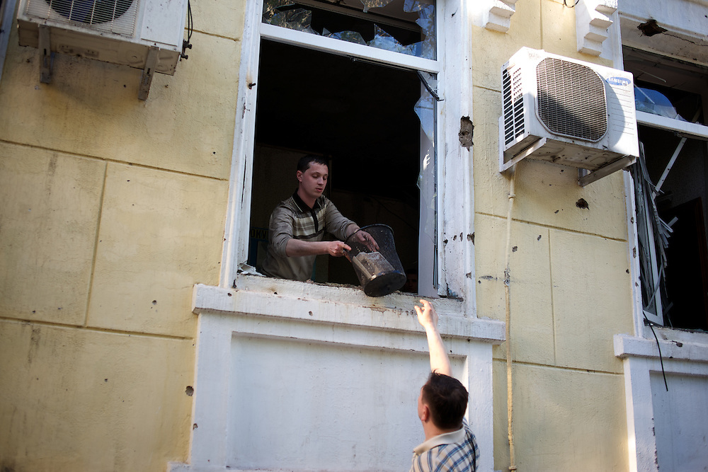 Civilians recover objects from  Mariupol's police headquarters, set ablaze hours earlier during deadly confrontations between armed separatist groups and the Ukrainian army over the control of key buildings throughout the city.