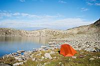 Backpacking tent camp on shore of lake Blørnbøljønne on Besseggen trail, Jotunheimen national park, Norway