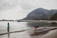 Jeju Island, South Korea - September 15, 2019: Two girls explore Hwasun Golden Sand Beach with their dad (not pictured) on Jeju Island, South Korea.