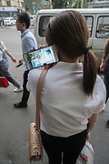 Woman standing on pavement in street, in conversation on mobile telephone. Beijing, China