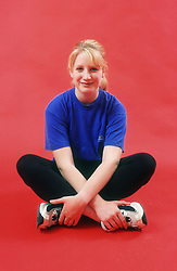 Teenage girl sitting cross legged resting after exercise session,