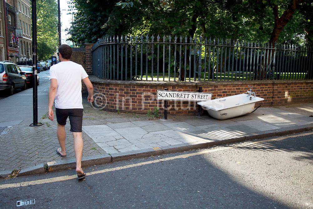 Discarded bath tub left on the street in Wapping, London, UK. Rather than pay for the collection of large items, it is common for fly tipping to occur where items are dumped on the street.