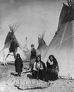 Commanding Officer inspecting the Sioux Indian Camp, also the Mediciine Tepee and flag of red flannel, with One Bull and Black Praire Chicken watching a hide that has just been stretched by  squaws, 1882.