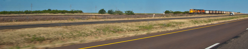 A BNSF (Burlington Northern Santa Fe) railroad freight train passes by along rural I-20 in west Texas, USA panorama