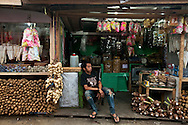A street vender sits outside his vegetable shop.<br /> Various scenes of the city of Jakarta in Indonesia.