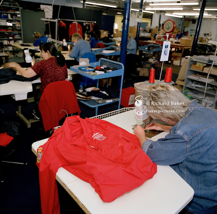 Senior Machinist Supervisor, Tricia Randle finishes a red flying suit of Squadron Leader David Thomas, a pilot of the elite 'Red Arrows', Britain's prestigious Royal Air Force aerobatic team. Tricia is a bespoke seamstress at Dale Techniche, Nelson, Lancashire. Every Winter, the Red Arrows place about 40 pilot suit orders and 180 blue (support ground crew) suits. Tricia adjusts her thread while the suit is complete on her work bench. The clothing factory also designs the Red Arrows badges, each requiring 15,000 stitches. All suits are made from Nomex by the Du Pont corporation, containing 5% Kevlar. Flame-retardant, they fit exactly each team member. Fouteen different measurements are taken before the first suit is cut, each one requiring approximately three metres of dyed cloth. When a suit is complete, each one is signed inside by the machinist.