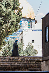 19 April 2019, Jerusalem: A woman passes by one of the entry points to Al Aqsa mosque in Jerusalem, from the Suq al Qattanin (the Cotton Market).