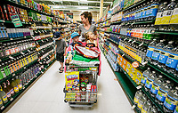 Kristi McCarthy goes down an aisle with her kids Franco, walking and Harrison and Bristol riding in a cart shaped like a car at Haggen grocery store in Palmdale, CA. April 5, 2015. Photo by David Sprague