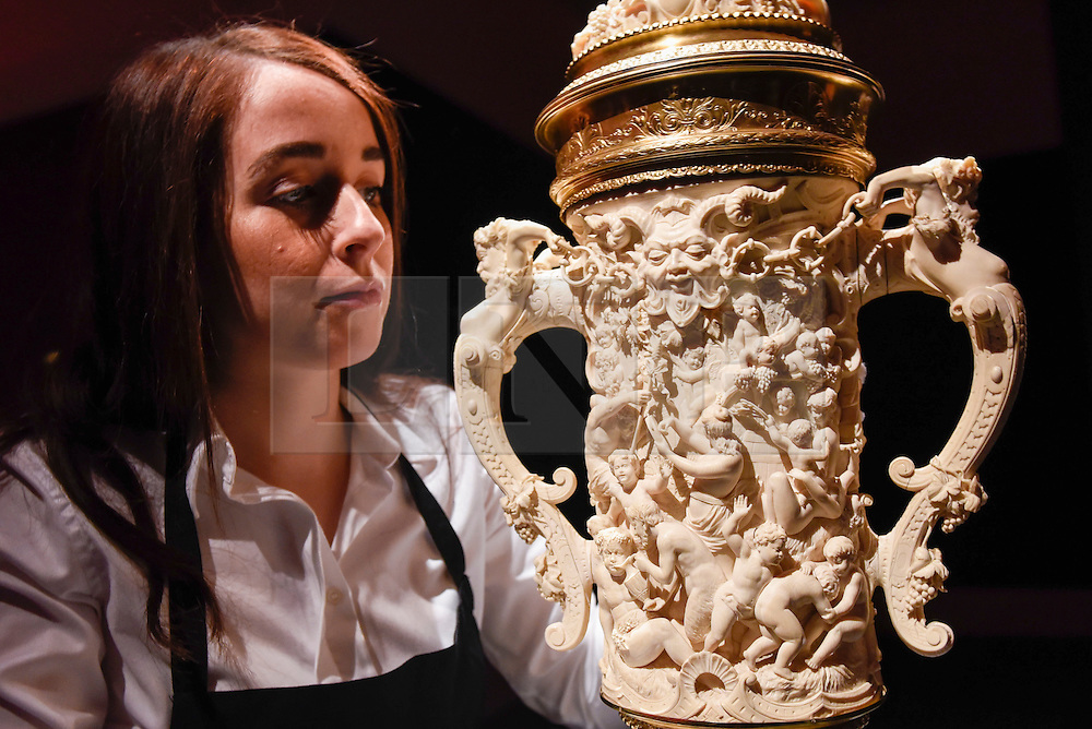"""© Licensed to London News Pictures. 10/02/2017. London, UK.  A technician inspects """"A Two Handled Tankard"""" by Neresheimer (est. GBP40-60k), at the preview of the """"Erotic: Passion & Desire"""" sale at Sotheby's in New Bond Street.  The sale, which will take place on 16 February, encompasses representations of love and sex from antiquity to the present day.  Photo credit : Stephen Chung/LNP"""
