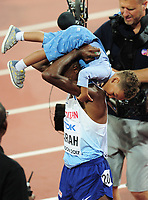 Athletics - 2017 IAAF London World Athletics Championships - Day One<br /> <br /> Mens 10,000m Mens Final<br /> <br /> Mohamed Farah (Great Britain) throws his son over his shoulder after winning the race, at the London Stadium.<br /> <br /> COLORSPORT/ANDREW COWIE