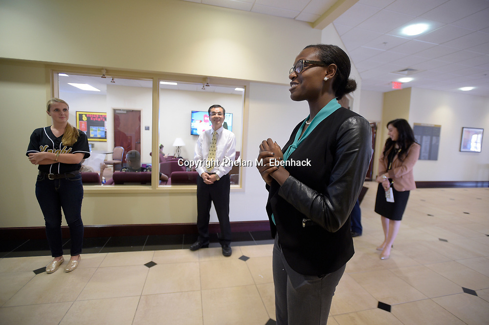 Hospitality management student DiJai Dowling, 21, second from right, answers a question during a tour of the Rosen College of Hospitality Management building at the University of Central Florida in Orlando, Fla., Tuesday, Aug. 25, 2015. Listening are student Abbie Kellner, 20, left, and Associate Dean Dr. Youcheng Wong, second from left. (Photo by Phelan M. Ebenhack)