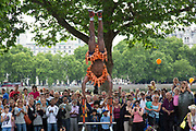 Juma the street performer with his balance and strength act performs to a large crowd gathered on the Southbank walkway. The South Bank is a significant arts and entertainment district, and home to an endless list of activities for Londoners, visitors and tourists alike.