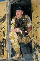 A British soldier,serving with the Muliti National Division in beret and desert camouflage sits in the back of an army armoured landrover with an SA80 assault rifle and SUSAT, at Basra Air Station during Op Telic Iraq 2005