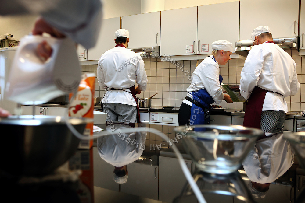 Inmates (all but the woman teacher in the middle) are taking part to a cooking lesson inside the luxurious Halden Fengsel, (prison) near Oslo, Norway.