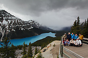 A group of tourists pose for a shot, as storm clouds build over the unfeasibly blue waters of Peyto Lake in Banff National Park, just outside Lake Louise. A few minutes ater this it was snowing, in mid-June!