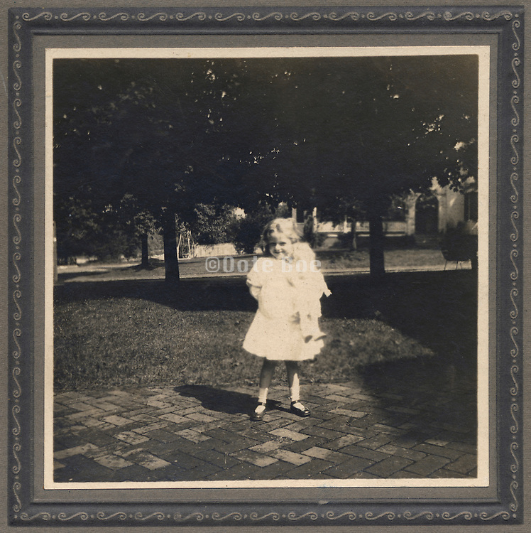 An old photograph of a child holding her doll