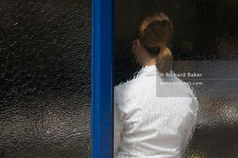 A lady waitress awaits lunchtime business, seen through the frosted window of Sweetings seafood restaurant, City of London.