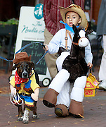 Mayu Marron, 4, dressed as a cowboy with his dog Tiger during the 7th annual Doggie Howl-O-Ween event Thursday night on the Downtown Mall in Charlottesville, VA. Over 20 Downtown businesses participated in the event that included a Doggie parade and Doggie costume contest. Photo/Andrew Shurtleff