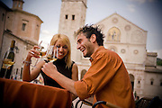A couple dines outside at a cafe in a downtown area of Spoleto, Italy.