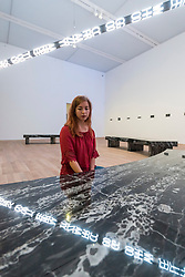 """© Licensed to London News Pictures. 20/07/2018. LONDON, UK. A staff member views """"FLOOR 2015"""", a large scale kaleidoscopic work, by Jenny Holzer at the preview of ARTIST ROOMS: Jenny Holzer at Tate Modern. The annual free display includes text-based installations and paintings by the American artist Jenny Holzer and runs 23 July to summer 2019.  Photo credit: Stephen Chung/LNP"""