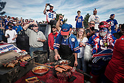 """SHOT 10/22/17 9:33:03 AM - Tailgating at the Hammer's Lot at the Pinto Ron tailgate party before the Buffalo Bills faced the Tampa Bay Buccaneers in Orchard Park, N.Y. Ken Johnson, better known as """"Pinto Ron"""", (born 1958) is a Buffalo Bills fan known for attending every single Bills home and away game and hosting a tailgate party since 1994. He is known for his red Ford Pinto and antics cooking food on his car hood in a variety of objects such as a shovel and army helmet; furthermore, he holds a tradition of being doused in ketchup and mustard. Most notably he served shots out of a bowling ball until he was forced to shut down by the National Football League (NFL) Johnson moved his tailgate party to private property next to the stadium where the NFL has no jurisdiction and was able to resume serving bowling ball shots. He has been featured in multiple NFL Films, as well as the made-for-TV movie Second String. (Photo by Marc Piscotty / © 2017)"""