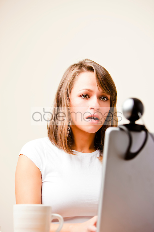 Woman using laptop computer with webcam
