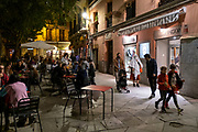 A woman dressed as a ghost walks past people sitting outside eating dinner and having drinks at a bar on the Plaza del Dos de Mayo during the Halloween celebrations on the 31st of October 2019 in Madrid, Spain. (photo by Andrew Aitchison / In pictures via Getty Images)