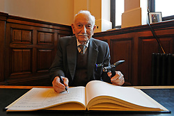 """© Licensed to London News Pictures. 02/02/2012, Kingston Upon Thames, UK. 104 year-old becomes Britain's oldest new citizen. Mr Khanjar signs the register. 104 year-old TAUFEEK KHANJAR became a British Citizen at a ceremony held by Surrey County Council today (01 February 2012). Mr Khanjar is originally from Iraq and worked as a jewellery maker in Baghdad. He came to the UK six years ago to live with his daughter Nada Dabis, 59, in South Cheam, Surrey, where he enjoys walking, feeding the birds, playing cards and listening to music. He is a widower with four sons and two daughters. Durning the ceremony Mr Khanjar took an oath to the Queen, pledging that he will be a faithful citizen and obey the laws of the country. He explained the secret to a long and healthy life was to """"never get stressed and be relaxed"""".  Photo credit : Stephen Simpson/LNP"""