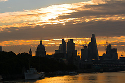 © Licensed to London News Pictures. 11/08/2017. LONDON, UK.  The sun rises behind clouds and St Paul's Cathedral and skyscrapers on the River Thames this morning. The capital has seen a cold start to day following a spell of wet weather this summer. Photo credit: Vickie Flores/LNP