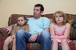 Father and daughters sitting on the sofa,