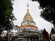 24 JUNE 2011 - CHIANG MAI, THAILAND: The chedi (pagoda) with Buddha statues, at Wat Bupparam in Chiang Mai, Thailand. Wat Bupparam is built in the Burmese style and was built by Burmese teak merchants who settled in Chiang Mai.   PHOTO BY JACK KURTZ