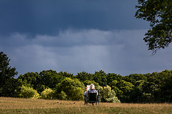 © Licensed to London News Pictures. 24/08/2020. London, UK. A man on a deckchair reads his newspaper in Richmond Park as dark clouds loom over South West London. Forecasters have warned that Storm Francis is set to batter the UK later to night with winds in excess of 50mph along with heavy rain. The Met Office has issued a yellow weather warning for high winds for most of the country which could lead to travel disruption and damage to trees. Photo credit: Alex Lentati/LNP