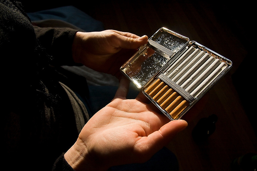 A young man holds open a vintage silver cigarette holder filled with cigarettes.