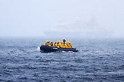 Tourists approach the Antarctic shore of Deception Island onboard a zodiac dinghy