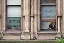 "© Licensed to London News Pictures . 23/10/2015 . Manchester , UK . A woman inside Manchester Town Hall by windows with "" TREASURER "" stencilled , in Albert as Chinese president , Xi Jinping , visits inside as part of his state visit to the United Kingdom . Photo credit: Joel Goodman/LNP"