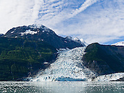 The tidewater Cascade and Barry Glaciers pour from the steep and glaciated Chugach Mountains into Barry Arm of Prince William Sound, Alaska, USA. Prince William Sound is surrounded by Chugach National Forest (the second largest national forest in the USA). Tour spectacular Prince William Sound by commercial boat from Whittier, which sits strategically on Kenai Peninsula at the head of Passage Canal. Whittier is a port for the Alaska Marine Highway System, a ferry service which operates along the south-central coast, eastern Aleutian Islands, and the Inside Passage of Alaska and British Columbia, Canada. Cruise ships stop at the port of Whittier for passenger connections to Anchorage (by road 60 miles) and to the interior of Alaska via highway and rail (the Denali Express). Known by locals as the Whittier tunnel or the Portage tunnel, the Anton Anderson Memorial Tunnel links Whittier via Portage Glacier Highway to the Seward Highway and Anchorage. At 13,300 feet long (4050 m), it is the longest combined rail and highway tunnel in North America. Whittier was severely damaged by tsunamis triggered by the 1964 Good Friday Earthquake, when thirteen people died from waves reaching 43 feet high (13 meters).