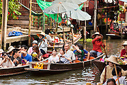 "10 JULY 2011 - DAMNOEN SADUAK, RATCHABURI, THAILAND:  Tourists photograph the floating market in Damnoen Saduak, Thailand. The Thai countryside south of Bangkok is crisscrossed with canals, some large enough to accommodate small commercial boats and small barges, some barely large enough for a small canoe. People who live near the canals use them for everything from domestic water to transportation and fishing. Some, like the canals in Amphawa and nearby Damnoensaduak (also spelled Damnoen Saduak) in Rajburi  province (also spelled Ratchaburi) are also relatively famous for their ""floating markets"" where vendors set up their canoes and boats as floating shops.    PHOTO BY JACK KURTZ"