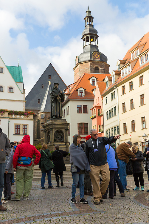 Cathy '72 and Phil Tribble '72 walk through the Eiselben town square with a statue of Martin Luther and St. Andreas Church behind them.
