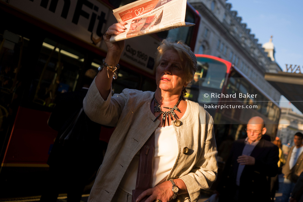 Woman shields her face from bright light along Piccadilly in late afternoon sunshine.
