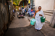 13 JANUARY 2013 - BANGKOK, THAILAND:  A Buddhist nun walks back to her temple in the Bang Luang neighborhood in Bangkok. The Bang Luang neighborhood lines Khlong (Canal) Bang Luang in the Thonburi section of Bangkok on the west side of Chao Phraya River. It was established in the late 18th Century by King Taksin the Great after the Burmese sacked the Siamese capital of Ayutthaya. The neighborhood, like most of Thonburi, is relatively undeveloped and still criss crossed by the canals which once made Bangkok famous. It's now a popular day trip from central Bangkok and offers a glimpse into what the city used to be like.     PHOTO BY JACK KURTZ
