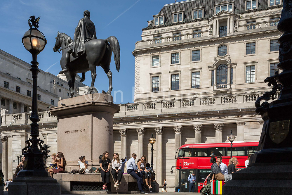 Lunchtime City workers enjoy warm summer sunshine beneath the Duke of Wellingtons statue that stands opposite the Bank of England right at Bank triangle in the City of London, the capitals financial district aka the Square Mile, on 22nd August 2019, in London, England.