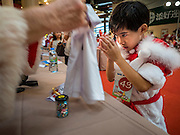 "17 SEPTEMBER 2015 - BANGKOK, THAILAND: A Thai boy dressed as a Christmas elf, ""wais"" a Santa Claus at the World Santa Claus Congress. The ""wai"" is the traditional Thai greeting. Twenty-six Santa Clauses from around the world are in Bangkok for the first World Santa Claus Congress. The World Santa Claus Congress has been an annual event in Denmark since 1957. This year's event, hosted by Snow Town, a theme park with a winter and snow theme, hosted the event. There were Santas from Japan, Hong Kong, the US, Canada, Germany, France and Denmark. They presented gifts to Thai children and judged a Santa pageant. Thailand, a Buddhist country, does not celebrate the religious aspects of Christmas, but Thais do celebrate the commercial aspects of the holiday.    PHOTO BY JACK KURTZ"
