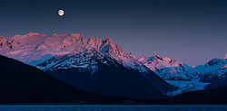 A full moon rises above Mount Ernest Gruering and the Herbert Glacier near Juneau, Alaska as the final rays of the sun at sunset baths mountain tops in alpenglow light. The view is from the Alaska Marine Highway System ferry FVF Fairweather as it traveled down the Lynn Canal from Haines.