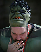 A man dressed as The Incredible Hulk smokes outside of the 2019 Emerald City Comic Con at the Washington State Convention Center, Friday, March 15, 2019.