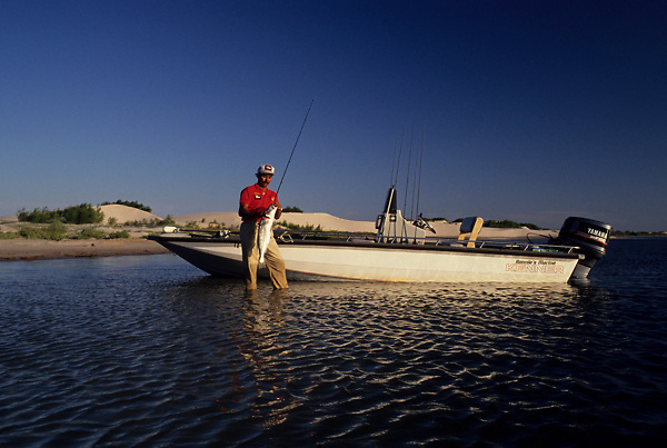 Stock photo of a man wading beside his boat and holding a fish that he just caught