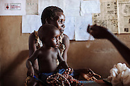 A worker for the nonprofit organization Papers to Pearls holds her son at Pabo Internally Displaced Persons Camp, northern Uganda.